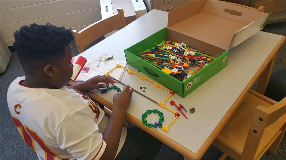 Student sitting at a table assembling K'Nex to form a two dimensional schoolbus.