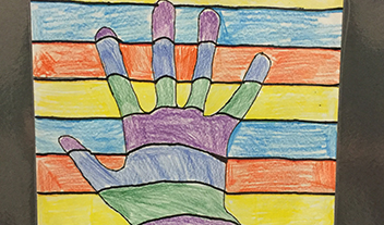 Student artwork shows colorful hand raised