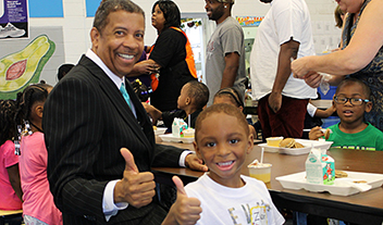 superintendent and prekindergartner giving thumbs-ups