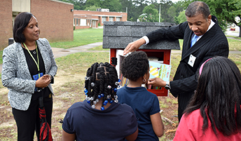 students selecting books from Little Free Library at Walnut Hill Elementary