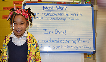 kindergarten student in front of writing wall